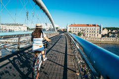 Милый велосипед катания женщины на мосте Стоковые Изображения