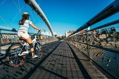 Милый велосипед катания женщины на мосте Стоковая Фотография RF