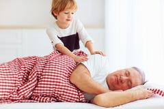 Милый внук нежно просыпает спрятанный grandpa вверх стоковая фотография