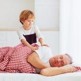 Милый внук нежно просыпает спрятанный grandpa вверх стоковое изображение