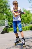 Милый девочка-подросток катаясь на коньках в парке конька стоковое фото rf
