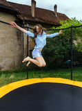 Милый девочка-подросток скача на батут стоковая фотография rf