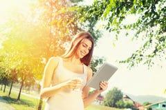 Милый девочка-подросток с таблеткой и кофе выноса в парке Стоковые Фото