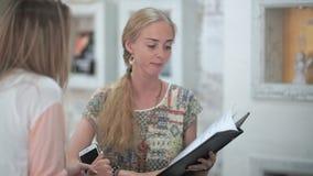 Милый девушк-консультант показывает каталог с типами обслуживаний к молодой женщине акции видеоматериалы