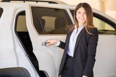 Милый женский водитель раскрывая автомобильную дверь стоковая фотография