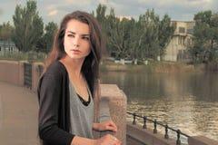 Милый ждать девушки ваш Носить светлый - серая рубашка, чернит куртку, загородку металла молодой американской женщины готовя даль Стоковое Изображение RF