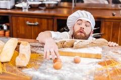 Милый забавный хлебопек шутя и имея потеху на кухне Стоковая Фотография RF