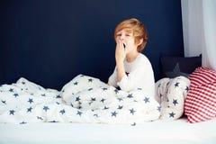 Милый зевая ребенк в пижамах сидя в кровати Стоковые Фотографии RF