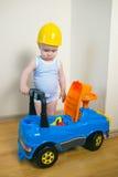 Милый и серьезный ребёнок ремонтируя автомобиль игрушки внутри помещения стоковые фото