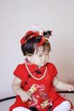Милый китайский маленький младенец в красных пузырях мыла игры cheongsam Стоковые Фотографии RF