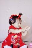Милый китайский маленький младенец в красных пузырях мыла игры cheongsam Стоковая Фотография