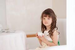 Милый коричнев-наблюданный чай девушки выпивая в ресторане Стоковое Изображение