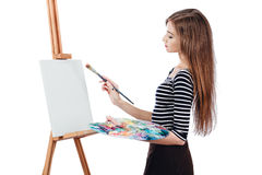 Милый красивый художник девушки крася изображение на мольберте холста Космос для текста Изолированная предпосылка студии белая, Стоковая Фотография RF