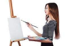 Милый красивый художник девушки крася изображение на мольберте холста Космос для текста Изолированная предпосылка студии белая, Стоковое Изображение RF