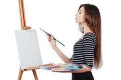 Милый красивый художник девушки крася изображение на мольберте холста Космос для текста Изолированная предпосылка студии белая, Стоковые Изображения RF