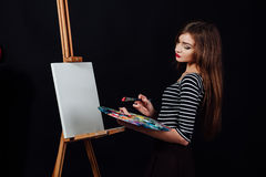 Милый красивый художник девушки крася изображение на холсте мольберт Космос для текста Предпосылка студии черная Стоковые Изображения RF
