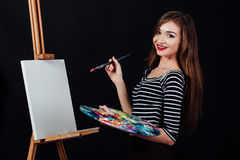Милый красивый художник девушки крася изображение на холсте мольберт Космос для текста Предпосылка студии черная Стоковое Изображение