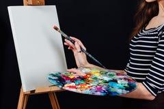 Милый красивый художник девушки крася изображение на холсте мольберт Космос для текста Предпосылка студии черная Стоковая Фотография