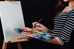 Милый красивый художник девушки крася изображение на холсте мольберт Космос для текста Предпосылка студии черная Стоковые Изображения