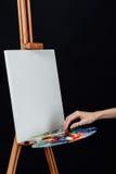Милый красивый художник девушки крася изображение на холсте мольберт Космос для текста Предпосылка студии черная Стоковые Фотографии RF