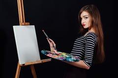 Милый красивый художник девушки крася изображение на холсте мольберт Космос для текста Предпосылка студии черная Стоковое Фото
