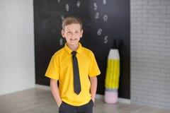 Милый красивый школьник в желтой связи футболки и cloase стильных ботинок вскользь стоящем для того чтобы почернить доску с номер Стоковые Фотографии RF