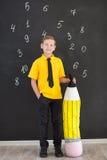 Милый красивый школьник в желтой связи футболки и cloase стильных ботинок вскользь стоящем для того чтобы почернить доску с номер Стоковая Фотография