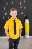 Милый красивый школьник в желтой связи футболки и cloase стильных ботинок вскользь стоящем для того чтобы почернить доску с номер Стоковые Изображения RF