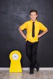Милый красивый школьник в желтой связи футболки и cloase стильных ботинок вскользь стоящем для того чтобы почернить доску с номер Стоковое Фото