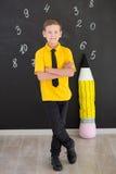 Милый красивый школьник в желтой связи футболки и cloase стильных ботинок вскользь стоящем для того чтобы почернить доску с номер Стоковая Фотография RF