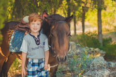Милый красный мальчик волос усмехаясь к камере и положению в лесе с лошадью Стоковое Изображение