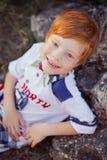 Милый красный мальчик волос усмехаясь к камере и положению в лесе с лошадью Стоковые Изображения