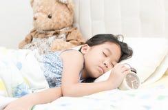 Милый маленький азиатский будильник сна и касания девушки на кровати в Стоковая Фотография