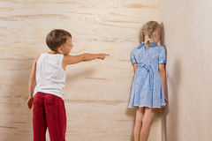 Милый маленький брат смеясь над к его сестре стоковая фотография
