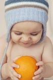 Милый маленький младенец сидя на кровати и держа апельсин Стоковые Фото