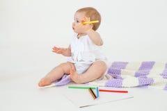 Милый маленький младенец сидя на поле на шотландке держа отметки Стоковые Изображения RF