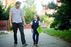 Милый маленький первый грейдер идет с его отцом к школе Стоковая Фотография RF