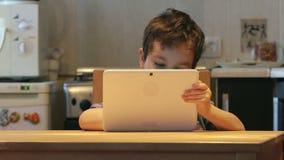 Милый маленький ребенок держит на руках белый ПК таблетки на таблице дома Вскользь одежды видеоматериал