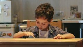 Милый маленький ребенок использует ПК таблетки на таблице дома Вскользь одежды видеоматериал