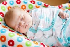 Милый маленький newborn спать ребёнка обернутый в одеяле Стоковые Изображения