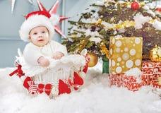 Милый маленький santa сидя в плетеной корзине Стоковые Фотографии RF