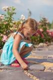 Милый малый чертеж девушки на тротуаре с мелом Стоковое Изображение RF