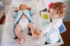 Милый малыш девушки помогая ее матери, изменяя пеленке младенца Стоковые Изображения RF