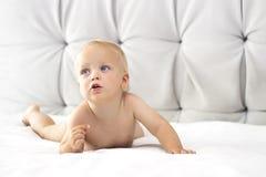 Милый малыш лежа на кровати и смотря прочь Стоковые Фотографии RF