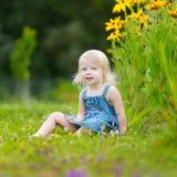Милый малыш маленькой девочки сидя на траве Стоковое Изображение