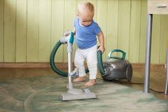 Милый малыш очищая вверх кухню с hoover Стоковая Фотография