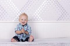 Милый малыш сидя на кровати и играя с smartphone Стоковое Изображение RF
