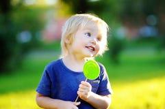 Милый малыш с большим зеленым леденцом на палочке Стоковое фото RF