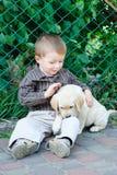 Милый мальчик вставать с его щенком labrador усмехаясь на камере Стоковое Изображение RF