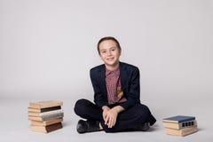 Милый мальчик в костюме сидя и усмехаясь на белой предпосылке Куча книг Стоковое Изображение